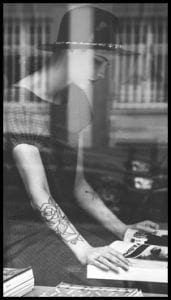 Magazine Association of BC Slider for home page: black and white image of woman with hat and tattoed arms looking at a magazine, photographed through a window with reflections