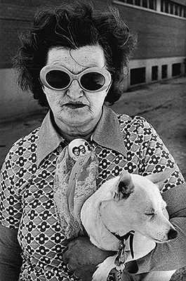 Older lady with funky sunglasses and lipstick carrying dog