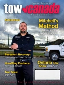 Tow Canada Magazine Cover Nov-Dec 2017, worker in black coverall with white truck and clouds in background