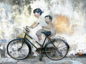 Mural of children. Looks like riding bicycle placed in front.
