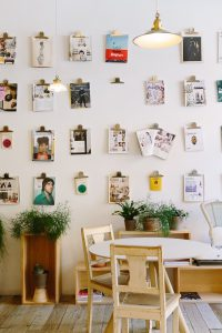Wall of magazine pages in front of table and chairs