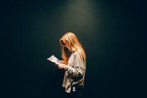 Woman reading magazine dark background