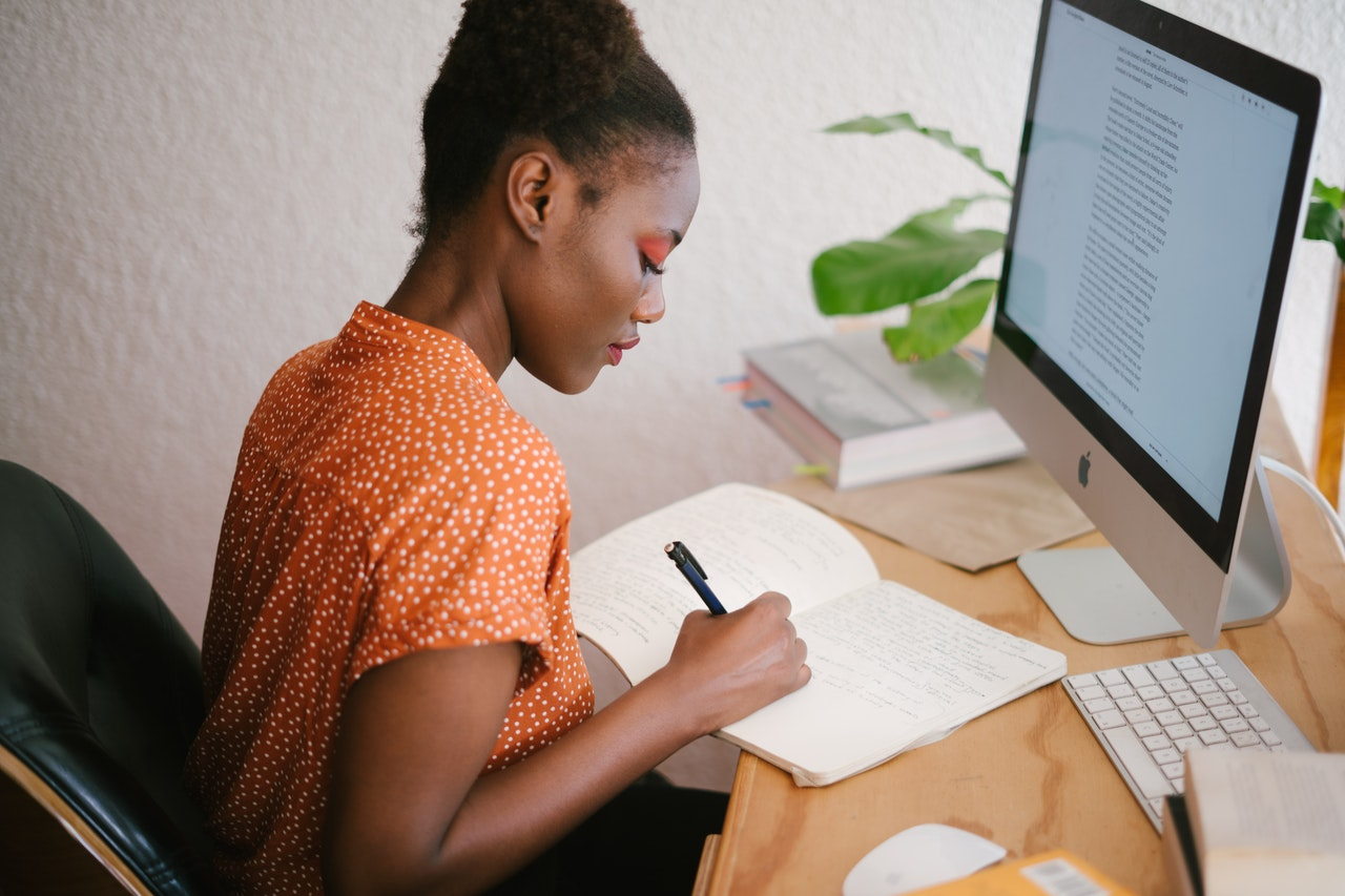 Woman writing in front of computer - Photo by Retha Ferguson from Pexels